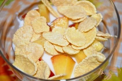 В креманку выкладываем на дно немного йогурта, сверху порцию персиков и хлопьев. Поливаем все йогуртом и снова персики и хлопья и т.д. Сверху должен оказаться слой йогурта.