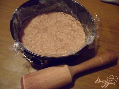 Форму покрыть пищевой плёнкой. Печенье с маслом утрамбовать по дну формы. Охладить в холодильнике пока готовится начинка.