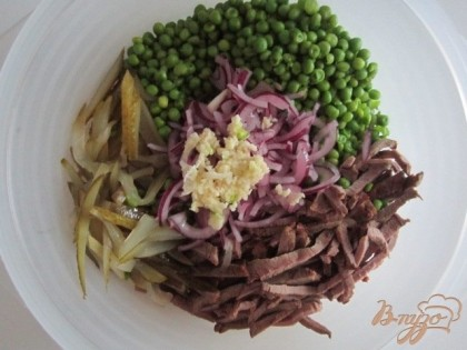В салатник уложить говядину, огурцы, зеленый горошек и лук.В серединку выложить нарезанный лук и выдавить чеснок. Отдельно накалить оливковое (растительное) масло до легкого дымка и вылить в середину салата, на лук с  чесноком. Хорошо перемешать.