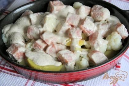 Картофель очистить и нарезать крупными дольками, капусту - сцедить, форму смазать маслом. Выложить в форму подготовленные овощи, сверху - рыбу и полить оставшимся соусом.