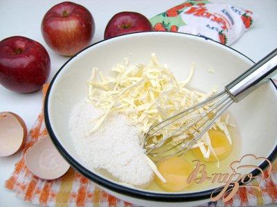 Яйца венчиком или миксером взбить с сахаром и маслом, натёртым на крупную тёрку.
