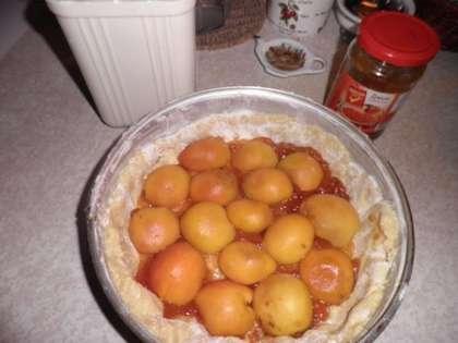 На выложенное в форму тесто выложить джем и абрикосы