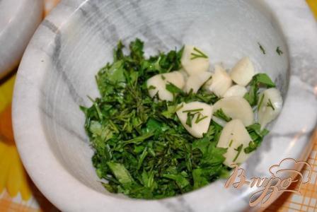 Тем временем очистите чеснок, вымойте зелень. Сложите все в ступку и хорошенько растолчите.Такая процедура раскрывает аромат чеснока и зелени.
