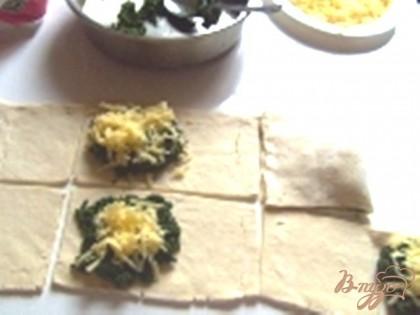 Режем тесто прямоугольниками, на одну сторону кладем шпинат и наверх тертый сыр, накрываем другой половинкой теста