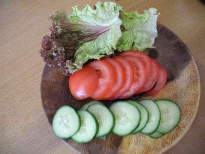 Салат вымыть и высушить, огурцы и помидоры нарезать колечками
