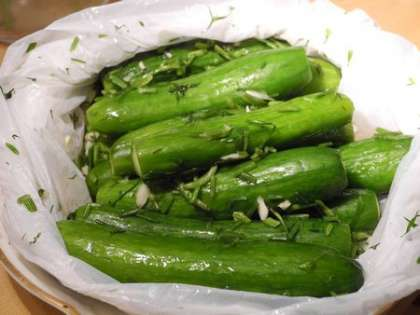 В пакет с огурцами добавить зелень с солью и перемешать