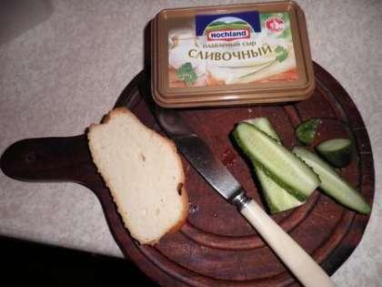 На хлеб намазать сливочный сыр и выложить тонкие пластинки огурца, предварительно просушив их полотенцем.