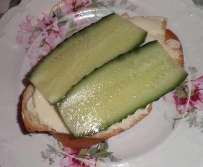 Отрезать 2 куска мягкого, белого хлеба.<br> Огурцы помыть, обсушить бумажным полотенцем и срезать кончики.<br> Порезать тоненькими пластинками вдоль огурца.<br> На хлеб намазать сливочный сыр.<br> Сверху положить по два кусочка огурца. <br>  Это вариант бутерброда. <br> Чтобы получился сэндвич надо сверху положить еще хлеб с сыром.<br>