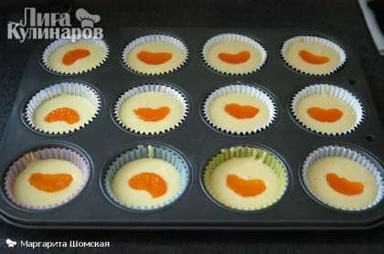 В форму для выпечки мини-сдобы  кладем на дно каждой ячейки ванильное печенье. Теперь выливаем в ячейки тесто для чизкейка. Ячейка должна быть заполнена примерно на ¾.