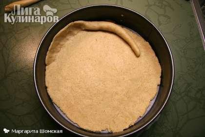 Из 2/3 теста раскатать основание пирога (равное диаметру дна) и уложить в форму. Из оставшегося теста скатать 2 валика диаметром 2 см и уложить внутри формы по краям. Расплющить по стенкам на 2-3 см вверх.