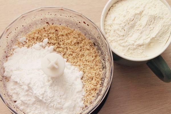 Поместите орехи в блендер, хорошо разотрите на большой скорости. Добавьте сахарную пудру, муку (1 стакан) и масло. Снова разотрите пока не получится однородная смесь.
