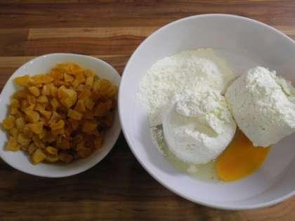 В глубокой миске смешать яйцо, творог и муку. Курагу промыть и мелко порезать