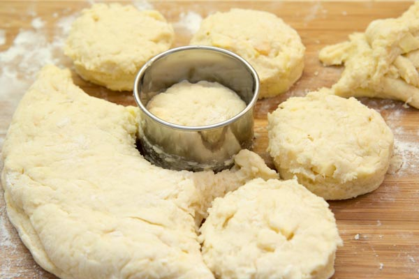 Подпылите рабочую поверхность мукой и раскатайте тесто до толщины 2,5-3 см. Кисточкой смахните лишнюю муку. Острым ножом разрежьте тесто на квадраты (примерно бхб см). У меня круги :)