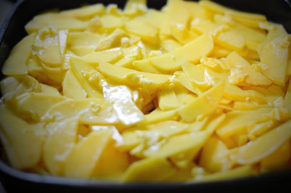 Смешать сливочное масло с чесноком, пропущенным через чеснокодавилку. Смазать картофель.