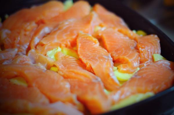 Порезать форель произвольными кусочками и уложить на картофель. Посолить.