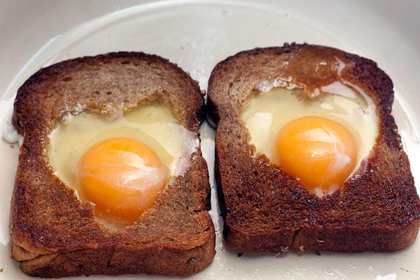 В хлебные окошки аккуратно разбейте яйца, стараясь не повредить желток. Жарьте на небольшом огне до нужной степени готовности.