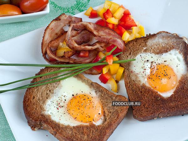 Подавайте яичницу в хлебе горячей, с поджаренным беконом и овощами.