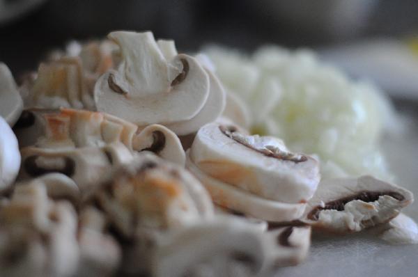 Пока запекается мясо, луковицу нарезать кубиками, немного обжарить на масле. Почистить и нарезать шампиньоны, добавить к луку. Посолить, поперчить, потушить под крышкой до готовности.