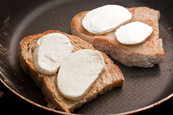 Пока варится яйцо, подсушите свежий хлеб на сковороде без масла, затем переверните и положите на него ломтики моцареллы.