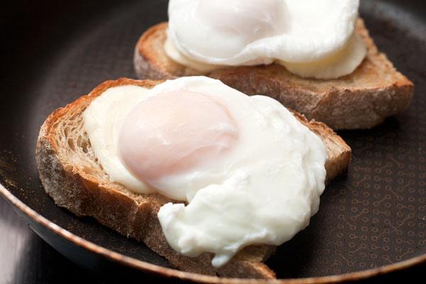 Готовые яйца выньте из кастрюли шумовкой, положите шумовку вместе с яйцом на чистое полотенце, чтобы впитались излишки воды.  Яйцо уложите поверх сыра.
