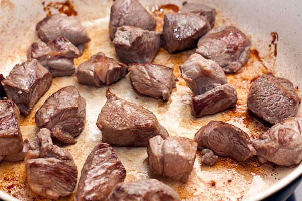 Мясо, подходящее для тушения, зачистите от жил и лишнего жира, нарежьте кубиками примерно 2 см.  Обжарьте небольшими порциями без масла на хорошо разогретой сковороде.