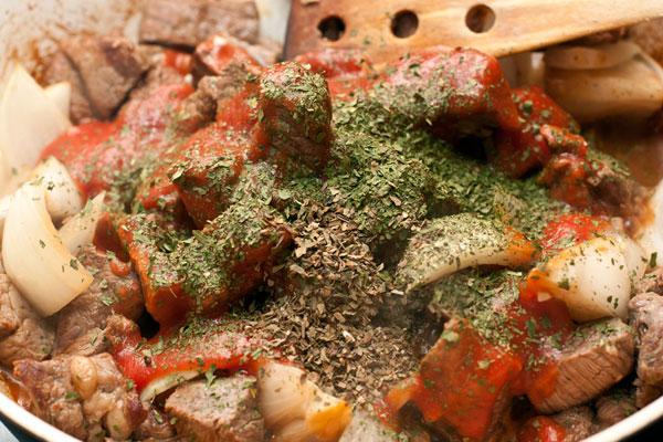 Добавьте томатное пюре, уксус, соль, перец и травы. Влейте воду (300-400мл) или бульон.