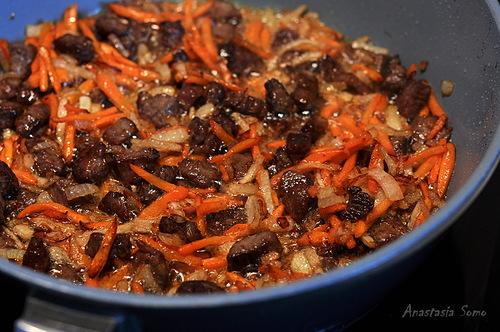 Разогреть масло и обжарить в нём цельную очищенную луковицу (у меня чеснок). Когда она станет золотистого цвета, а масло окрасится, убираем её.  Кладём баранину и обжариваем. Добавляем мякоть помидоров, нарезанные лук и морковь, продолжаем жарить. Солим, перчим.