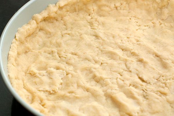 Охлажденное тесто раскатайте в тонкий пласт и выложите им форму для выпечки.   Сильно охлажденное тесто можно также натереть на терке или нарезать кусочками, которые распределить в форме.