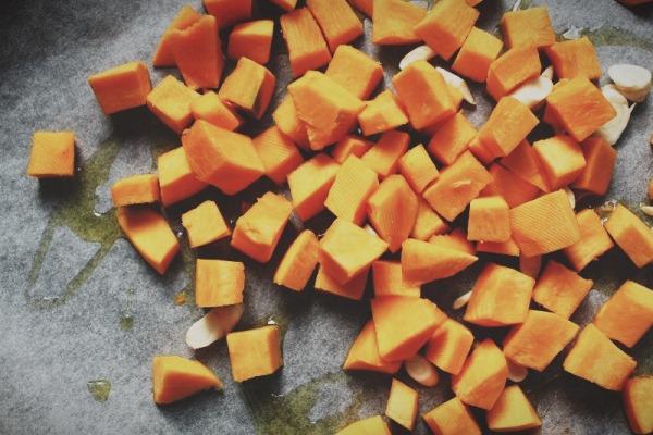Застелите противень бумагой для выпечки, смажьте ее оливковым маслом и выложите на нее овощи.