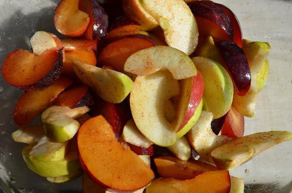Яблоки и сливы помыть, удалить сердцевину и косточки. Нарезать дольками. Смешать, добавить корицу, немного лимонного сока и рома. Накрыть и отставить в сторону.