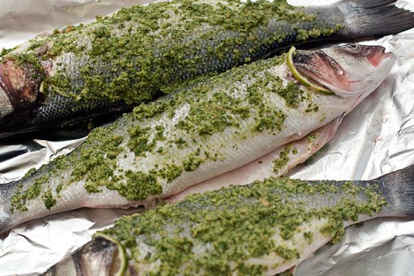 Рыбу обмажьте получившейся смесью снаружи и изнутри. Положите на противень, выстеленный фольгой.