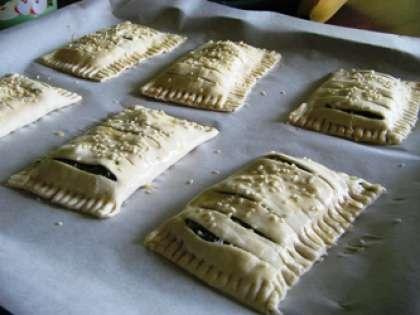 Сформировать прямоугольный пирожок, защипнуть края вилкой. Слойки выложить на противень, смазанный маслом. Верх пирожков смазать яичным желтком. Разогреть духовку. Противень с пирогами поставить в духовку. Выпекать около 20 минут.