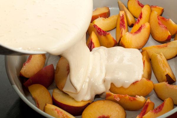 Вылейте тесто на персики.