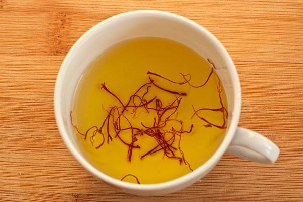 15-20 волокон шафрана замочите в небольшом количестве воды на 15 минут, чтобы вода окрасилась в интенсивный желто-оранжевый цвет.