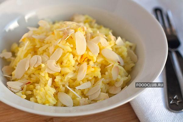 Разложите рис по тарелкам, посыпьте чуть поджаренными хлопьями миндаля.  Подавайте горячим в качестве гарнира или самостоятельного блюда.