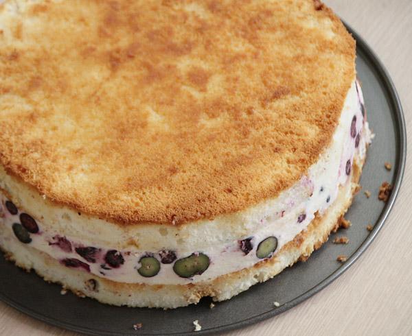 Пока желатин не схватился соберём торт. В форму для выпечки положите корж, на нём аккуратно разровняйте начинку и накройте вторым коржом. Уберите конструкцию в холодильник для полного застывания. Для этого может понадобиться пара часов. Готовый торт выньте из формы. Можно аккуратно обрезать края.