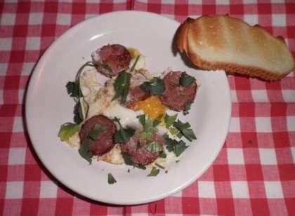 Готовую яичницу выложить на тарелку и посыпать свежей зеленью