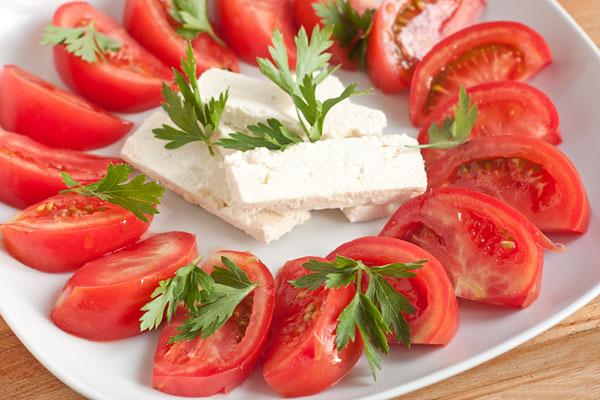 Листочки петрушки положите поверх помидоров и брынзы.