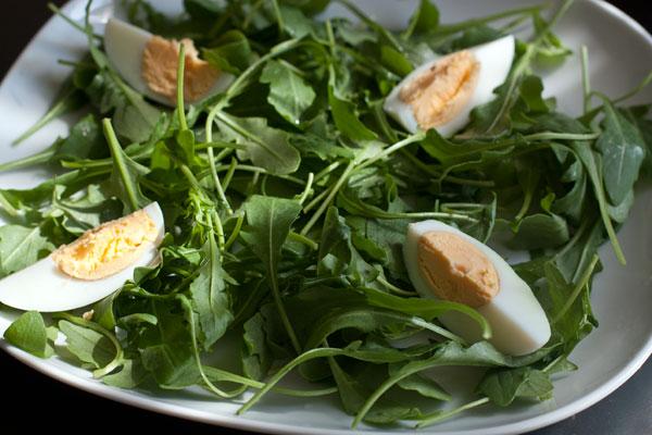 Вымытую и высушенную рукколу разложите на тарелках, сверху положите яйцо, разрезанное вдоль на 4 части.