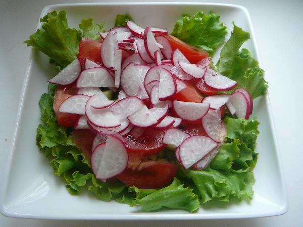 Рвем  руками салат, кладем в тарелку, выкладываем на него овощи.