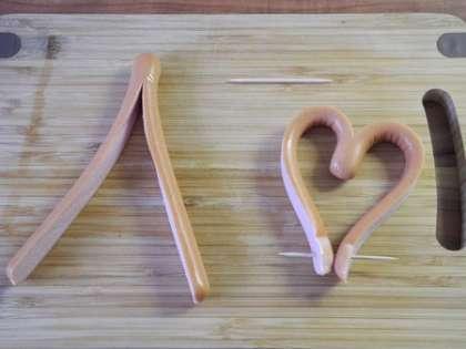 Сосиски разрезать вдоль, оставим неразрезанным кончик, примерно 2 см. Завернуть сосиску в виде сердечка, заколов ее зубочисткой
