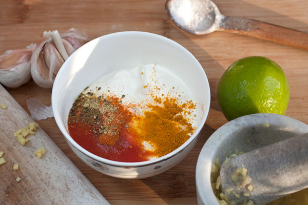 Очищенный чеснок растолките в ступке с морской солью и мелко нарезанным имбирем. В мисочке смешайте йогурт, столовую ложку томатного пюре, куркуму, порошок чили и сок лайма, добавьте содержимое ступки.