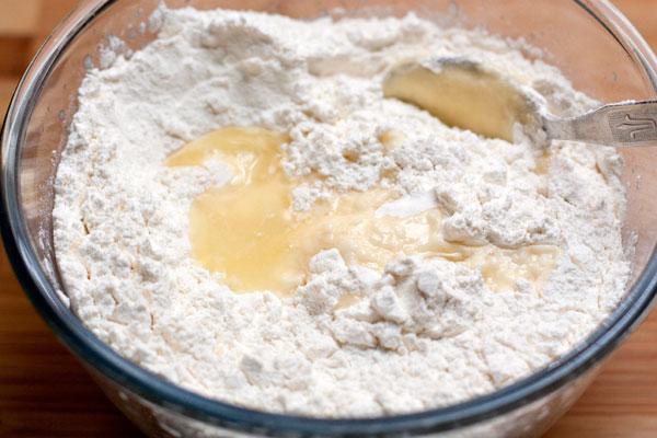 Всыпьте просеянную муку и добавьте 1-2 ложки рома или очень холодной воды.