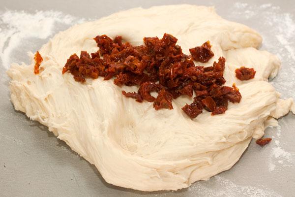 Сушеные помидоры выньте из масла, мелко нарежьте и вмешайте в готовое тесто.