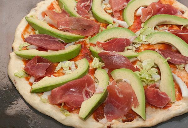 Разложите на пицце авокадо, кусочки ветчины и голубого сыра.