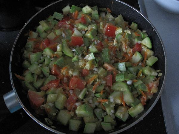 Яйца слегка взбить и полить ими овощи, перемешать так, чтобы овощи полностью покрылись яйцом. Сверху посыпать измельченным чесноком. Закрыть крышкой и дать яйцам приготовиться.