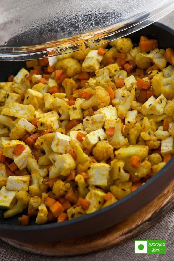Для приготовления этого блюда можно использовать любые овощи – баклажан, кабачок, стручковую фасоль, белокочанную капусту. Сегодня же мы возьмем цветную капусту и морковь.    Овощи и адыгейский сыр режем на небольшие кубики. На сковороде хорошо разогреваем масло и жарим - сначала кумин, через 1 минуту засыпаем все остальные специи, а через секунд 10 добавляем овощи и сыр. Обжариваем всё минут 5.