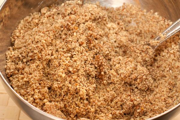 Всыпьте измельченные орехи в миску и перемешайте.