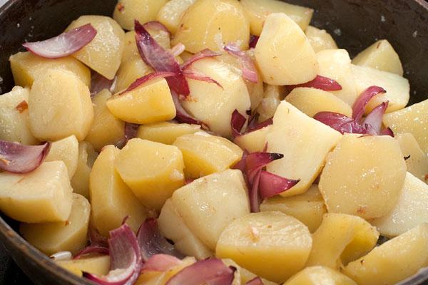 В сковороду добавьте картофель, перемешайте, чтобы он равномерно покрылся маслом и жарьте на среднем огне, неплотно прикрыв крышкой около 25 минут. Несколько раз осторожно перемешайте в процессе приготовления.  Посолите и поперчите по вкусу.