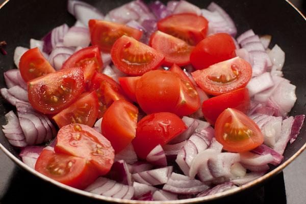 К луку добавьте крупно нарезанные помидоры (на фото  сорт чуть крупнее черри).